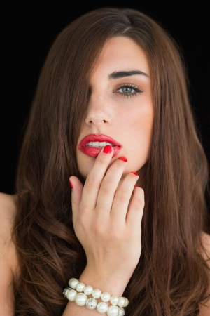 Brunette woman touching her red lips photo