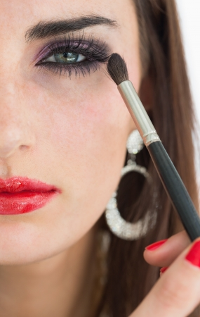 applying lipstick: Woman applying eye shadow while looking at camera