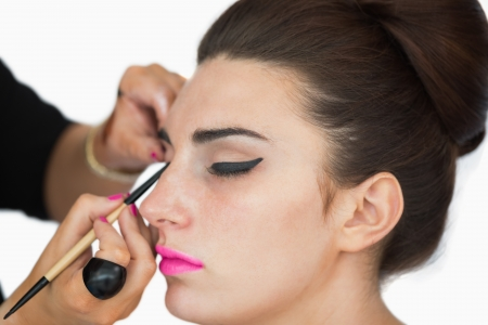 Woman with pink lips getting applied cat eyes photo
