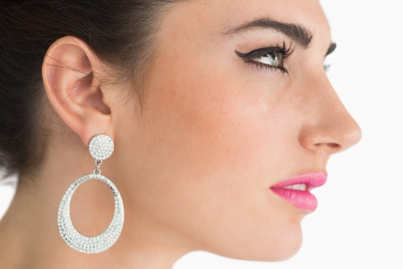 Woman wearing earrings in sixties makeup on white background photo