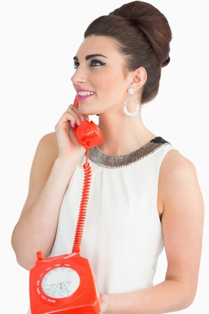 Sixties style Woman using old red dial phone on white background photo