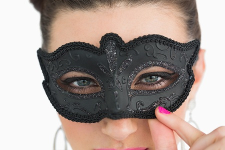 Woman wearing black masquerade mask on white background photo