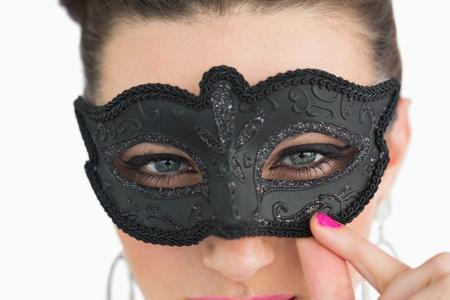 Woman wearing black masquerade mask on white background photo