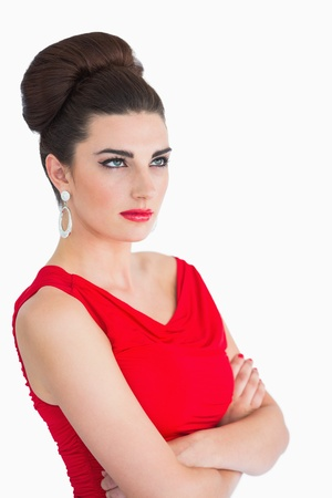 Woman in red dress having arms crossed and looking up photo