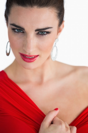 Glamorous woman touching her red dress while looking at camera photo