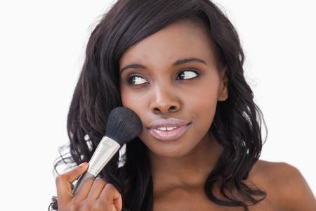 mooie vrouwen: Vrouw met behulp van make-up borstel op een witte achtergrond