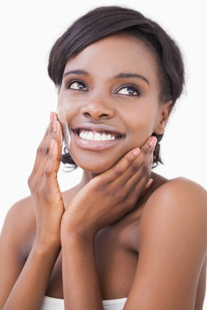 black woman face: Happy woman putting on face cream on white background Stock Photo