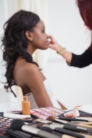 Table full of makeup with woman getting made over by make up artisit photo