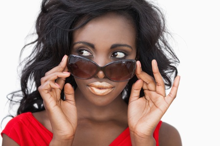 tilting: Woman tilting sunglasses against white background Stock Photo