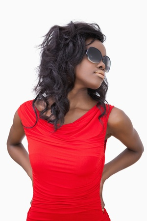 Woman wearing sunglasses with hands on hips against white background  photo