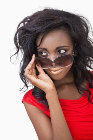 Woman wearing sunglasses while looking against white background photo