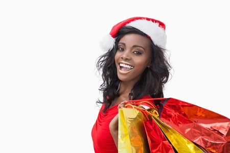 Woman wearing Santa Claus hat while holding bags photo