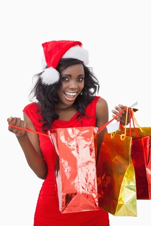 Woman holding bags wearing Santa Claus hat while smiling  photo