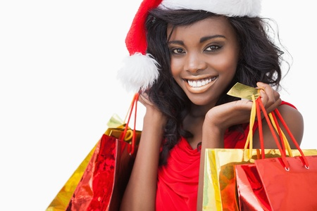 Festive woman standing looking while holding bags and smiling  photo
