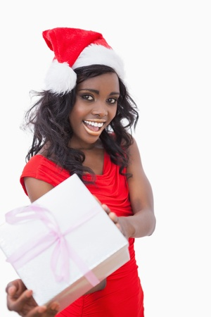 Festive woman standing holding a gift and smiling  photo
