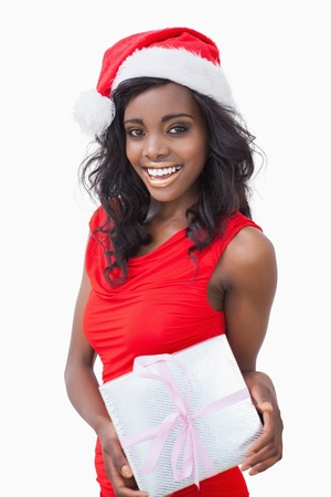 Woman standing holding a gift while smiling against white background photo