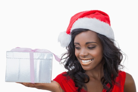 Woman standing looking at a gift against white background photo