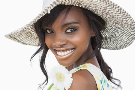 sun hat: Woman smiling and holding white flower in a sun hat against white background