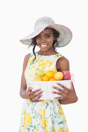 woman with sun hat and dress holding box with fruits photo