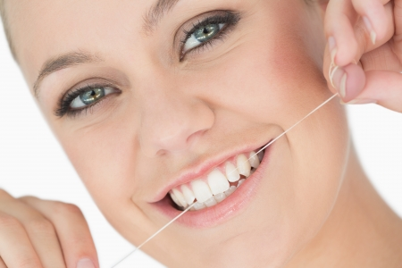 Woman using dental floss in the white background photo