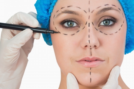 Plastic surgeon drawing on womans face for face lift
