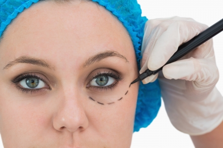 Plastic surgeon writing on the serious womans face in the white background photo