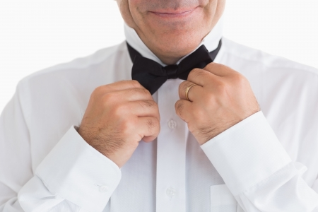 black tie: Smiling man fixing bow tie on white background