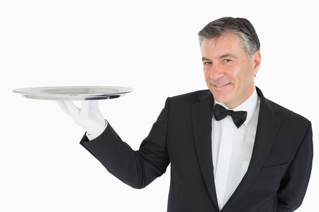 Waiter holding a silver tray and smiling Stock Photo - 16069831