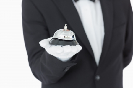 Well-dressed man holding a hotel bell in front of camera photo