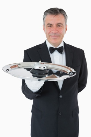 Well-dressed waiter holding a hotel bell in front of camera photo