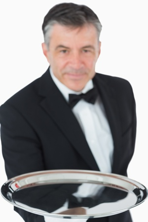 Waiter holding out silver tray on white background photo