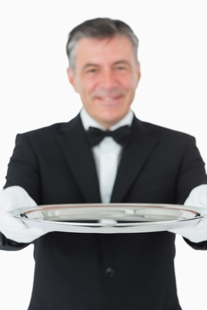 Waiter looking at the camera while holding a silver tray on white background photo