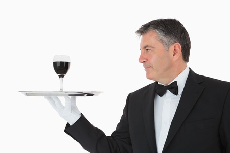 Happy waiter holding a glass full of wine on a silver tray on white background photo