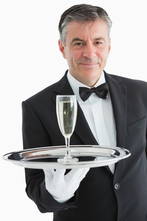 Smiling man serving champagne on silver tray photo