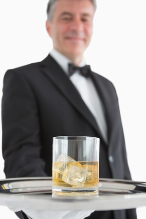 Smiling man in suit holding glass of whiskey on silver tray photo