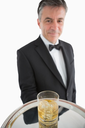 Smiling man serving whiskey with ice on silver tray photo