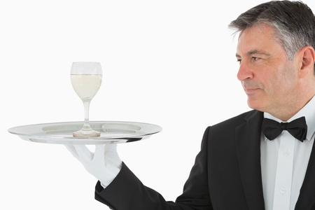 Man serving glass of white wine on silver tray
