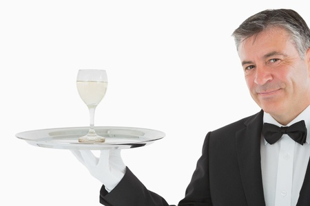 Smiling man in suit serving glass of white wine on silver tray photo