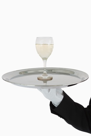 Glass of white wine on silver tray held by waiter photo