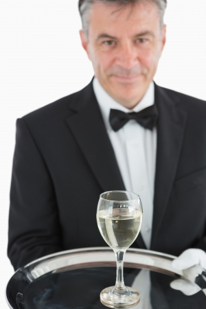 Waiter in suit serving glass of white wine on silver tray photo