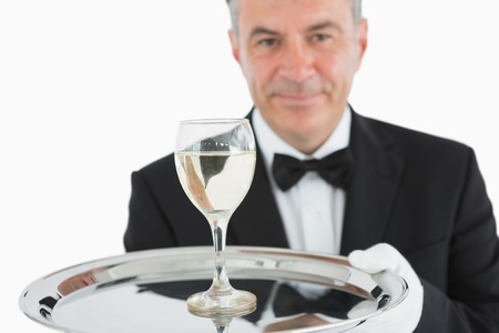 Smiling man in suit serving glass of wine on silver platter photo