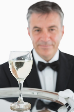 White wine on silver tray held by smiling waiter photo