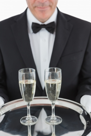 Man holding silver tray with three champagne flutes photo