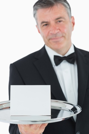 Waiter holding silver tray with white paper photo