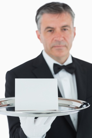 Man with serious face holding silver tray with white card photo