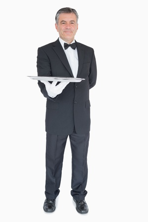 Waiter in suit holding silver tray photo