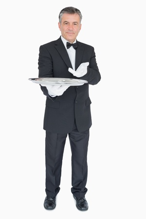 Man in suit showing us something on silver tray on white background photo