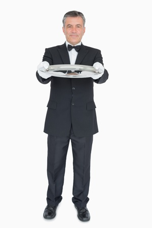Waiter in suit showing us empty tray photo