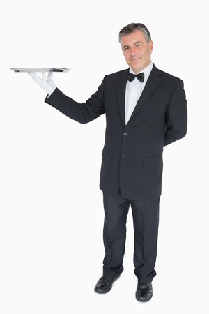 Smiling waiter holding empty silver tray photo