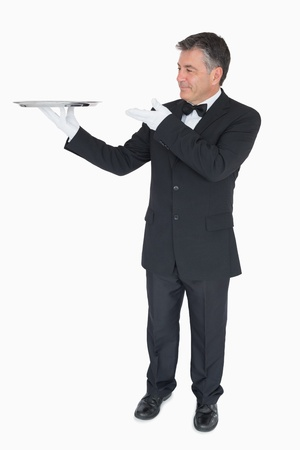 Waiter presenting empty silver tray on white background photo